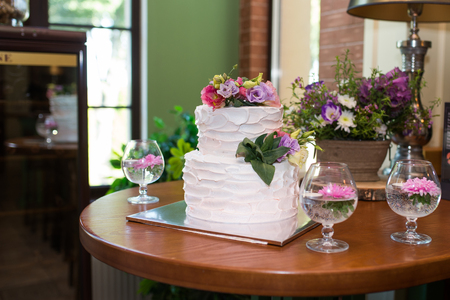 White 2 tiered wedding cake decorated with pink and lilac flowers on the top. Traditional Two Tiered White Wedding Cake with Flowers. Restaurant Stock Photo