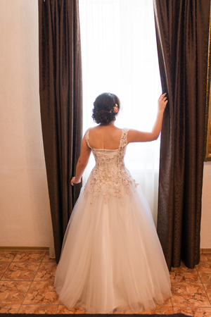 The bride stands near the window with. Wedding