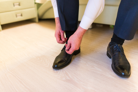 Groom wearing shoes on wedding day, tying the laces and preparing. Business man dressing up with elegant shoes. Stock Photo