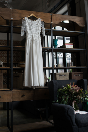 Rustic white wedding dress hanging on the cupboard. Loft interior 版權商用圖片
