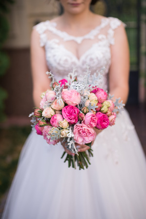 Bride holds in her hands wedding bouquet with pink roses. Wedding bouquet