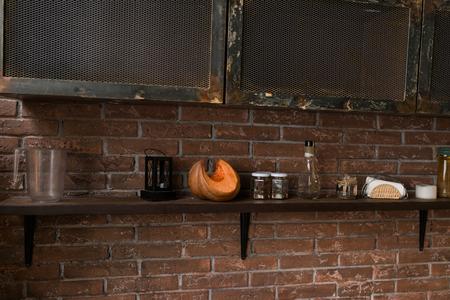 호박의 조각, 향신료의 항아리와 선반에 손전등. 배경에 벽돌 벽입니다.