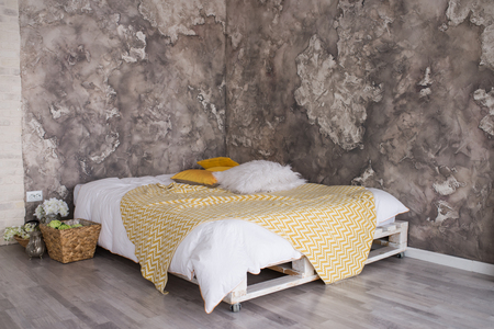 A loft style bedroom with recycled pallet bed. White and yellow bedding on bed with bedhead in loft