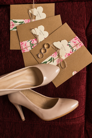 Wedding invitations in the craft envelopes, golden rings and a beige bridal shoes lying on a red armchair. Wedding concept. Wedding accessories.
