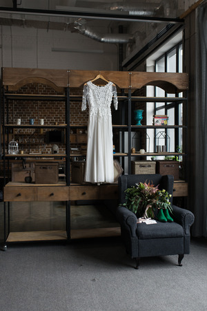 Green bridal shoes, green wedding bouquet with pink ribbons and a wedding complimentary lying on a gray armchair. Rustic white wedding dress hanging on the cupboard. Loft interior. Wedding details. 版權商用圖片