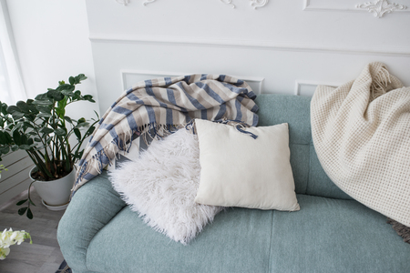 Two decorative pillows and bedspreads lie on a blue sofa. Cozy home 版權商用圖片