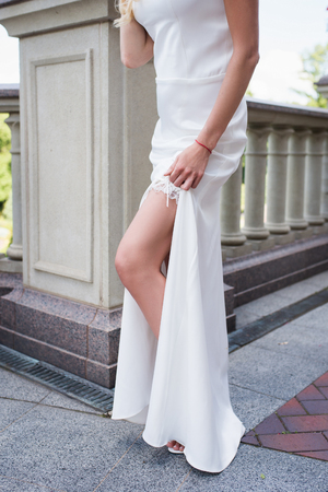Bride shows her tanned slim leg with garter