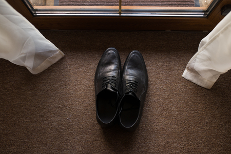 Black mens leather shoes on a brown background. Wedding details.