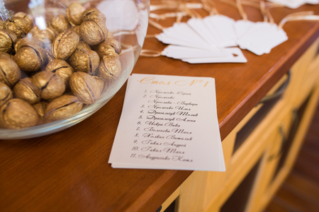 Golden walnut in a glass round vase and a guest seating list. Wedding decor