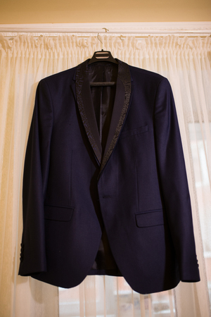 Beautiful blue grooms jacket hanging on the window for morning wedding preparation. Grooms accessories