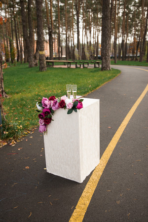 Two glasses with champagne stand on a pedestal with flowers in the park. Wedding details