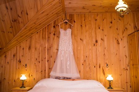 Wedding beige dress on the hanger in the room. Beautiful gown. Wedding