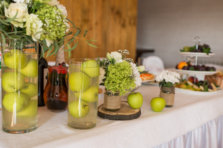 Rustic flower arrangement with white flowers and greenery in a glass vase with water and apples at a wedding banquet. Table set for an event party or wedding reception. 版權商用圖片 - 98402582
