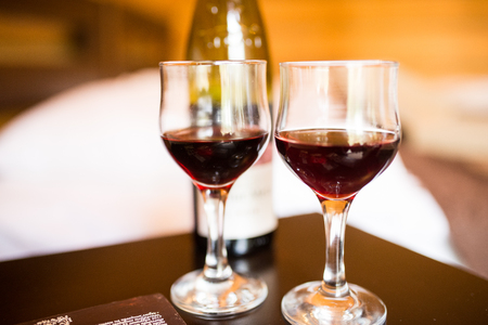 Two glasses are filled with red wine. Near the wineglasses stand a bottle of wine and a few chocolates lying. 版權商用圖片