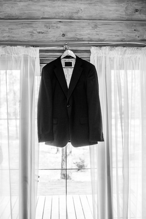 Beautiful grooms jacket hanging on the window for morning wedding preparation. Grooms accessories. Black and white photo.
