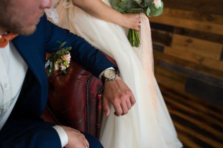 Groom in blue suit looking at his watch.