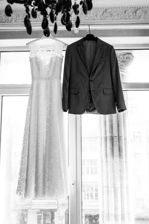 Bridal dress and a grooms suit on the hangers on a window. Wedding concept. Black and white photo.