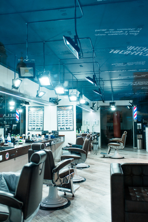 Vertical shot of empty chairs in retro styled barbershop. Hair salon interior. Interior of a barbershop, armchairs for clients