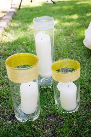 Three white candles are standing in a glass vases on the grass. Decor 版權商用圖片