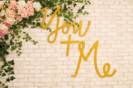 Brick background with the inscription You + me and a lot of flowers. Decoration.