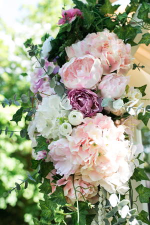 A part of the beautiful wedding arch with pink flowers and greenery in the garden