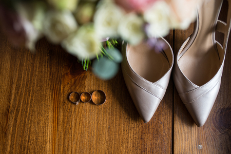 Golden wedding rings, engagement rings and a bridal beige shoes on brown background. Bridal accessories.