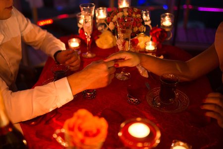 The bridegroom holds the bride's hand. Romantic date with a lot of burning candles, flowers and champagne. Love 版權商用圖片 - 98767949