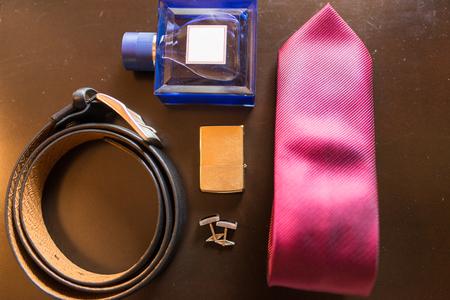 Grooms accessories: leather belt, cufflinks, perfume, necktie, cigarette lighter. Wedding 版權商用圖片