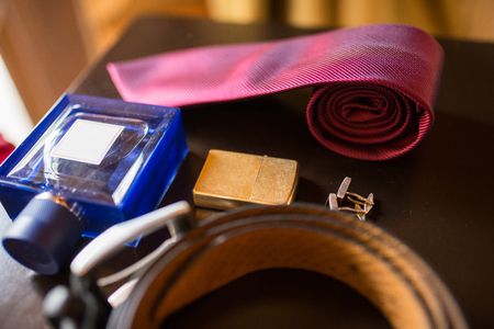 The grooms wedding accessories. Blue perfume and cigarette lighter in focus, leather belt and red necktie. 版權商用圖片