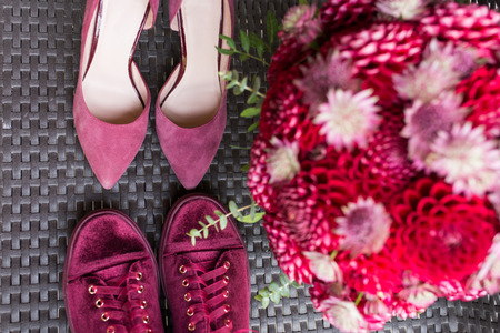 Wedding Heels VS bridal sneakers. Red wedding bridal accessories: bridal heels and sneakers of marsala color, red bridal bouquet from dahlias. Wedding details.