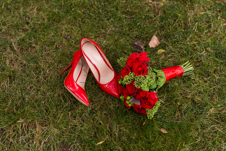 Female fashion red wedding shoes with brides bouquet of red roses and green berries on green grass background.