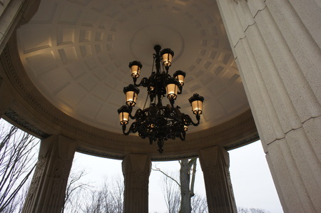 An ancient chandelier with light bulbs hanging in a lounger on the street