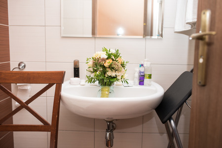 Wedding bouquet lies in the washbasin in the bathroom. Wedding chaos in the morning