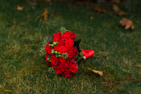 Wedding bouquet with red roses and green berries lying on a green grass. Bridal bouquet. 版權商用圖片 - 98672552