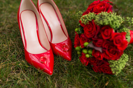 Two golden wedding rings lie on red fashion female shoes on green grass. Wedding details