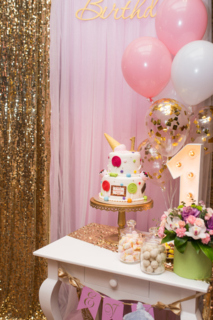 Two tier colorful childs cake for the first year old. Childrens photo zone with sweets and a balloons. Decorations for a One year old Girls Birthday party. Concept of childrens birthday party.