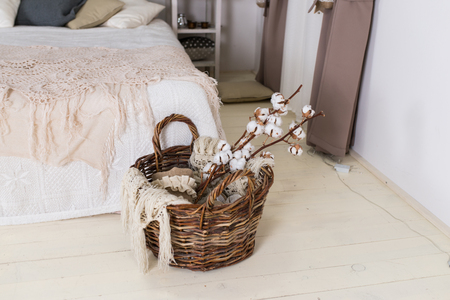 Beautiful white cotton flowers lie in a wooden basket near the bed.