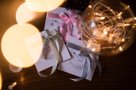 Three gift photoshoot cards with colorful ribbons near the lights garland in the vase 版權商用圖片 - 98820542