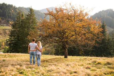 Happy girl and boy holding each other and walking in nature at autumn. The girl and boy in gray T-shirts and jeans, tenderly embracing each other. 版權商用圖片