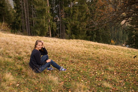 A young beautiful girl with long hair in a blue hoody is sitting on the mountainside. The girl closed her eyes. Autumn