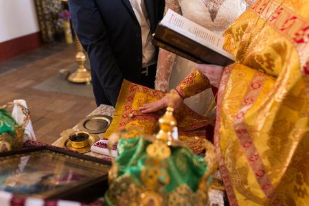 Priest holding bride's and groom's 版權商用圖片 - 98732415
