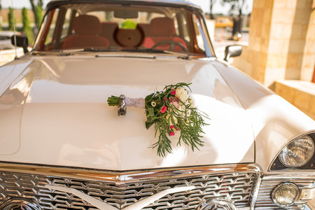 Lush bridal bouquet with white and pink flowers with a lot of greenery lying on the hood of white car of bride and groom.
