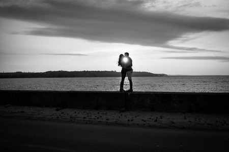 Couple in love on the background of beautiful sunset. Black and white photo. 版權商用圖片