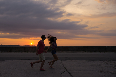 Couple in love running on the background of beautiful sunset 版權商用圖片 - 98676072