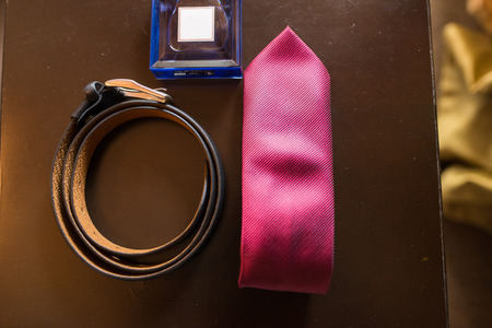 Grooms accessories: leather belt, blue perfume and red necktie. Wedding