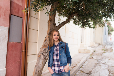 Smiling Caucasian girl. A girl with long hair in a denim suit leaned her elbows on the olive tree. Summertime