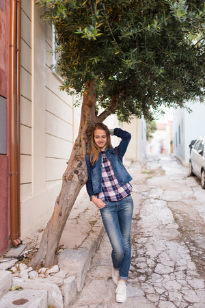 A girl with long hair in a denim suit and white sneakers leaned her elbows on the olive tree 版權商用圖片