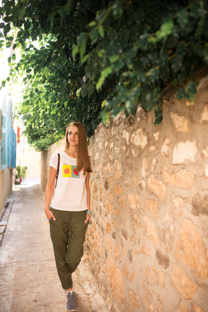 Caucasian girl in white T-shirt with fruits, green pants and gray sneakers is walking along a narrow ancient street with trees and blue shutters in the windows of the houses.