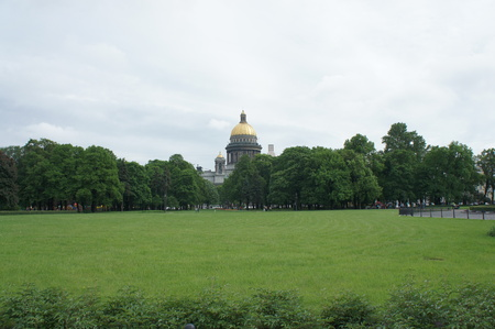 Park in front of the famous Isaac cathedral in Saint Petersburg, Russia. Natural lawn showing a wide field of green grass, with trees and domes in the background.