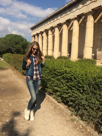Smiling Caucasian girl in sunglasses. A girl with long hair in a denim suit and white sneakers the girl walking along the ancient temple with columns. Summertime
